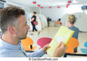 handsome youngman reading a document at a waiting area