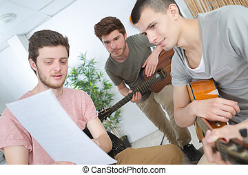 young man explains to the guitar players his party
