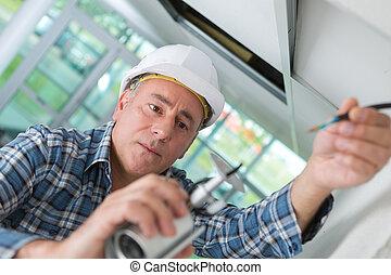 old worker in white helmet repairing