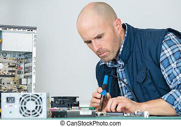 man fixing a microchip