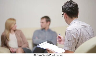 male psychologist helping worried young couple. family...