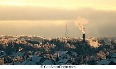 Iced trees, snowy roofs and smoking pipe at sunset 4K long...