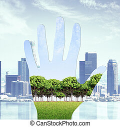 Nature concept - Abstract image of hand with green landscape...