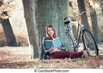Lady reading under tree. - Relax intellectual cycling...
