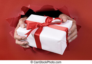 White gift with ribbon being delivered through a red torn paper background.