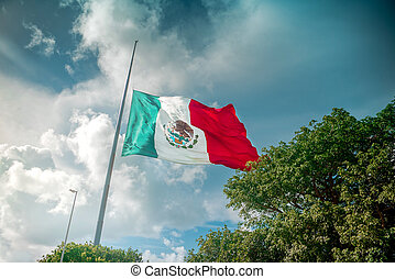 Giant mexican flag flies in the wind in Cancun. Shot in...