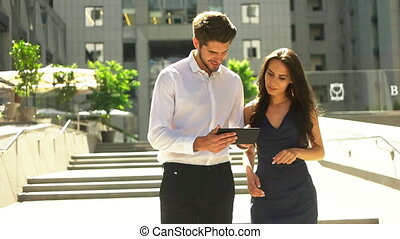 Two young collegues walking on the street, man holding a tablet on his hands.