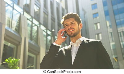 Young handsome businessman talking on mobile phone in the street.
