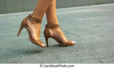 Close up of woman s legs walking outdoors in stylish summer shoes.