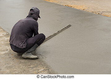 Workman finishes and smooths concrete surface. - Workman...