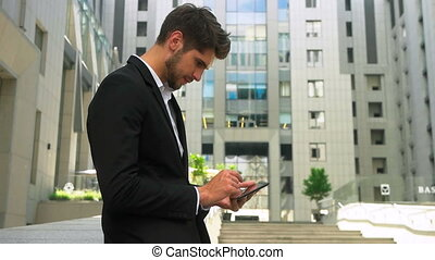 Young serious businessman using tablet and enjoying great...