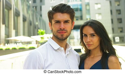 Two young smiling colleagues staying near modern business center and posing on camera.