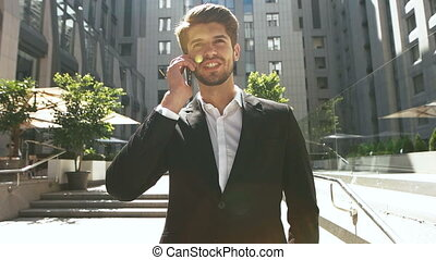 Young serious businessman talking with his partners on mobile phone.