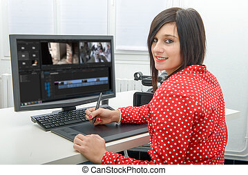 young female designer using graphics tablet for video...