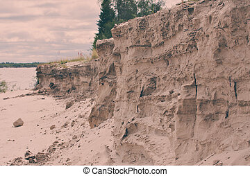 The dramatic steep sandy beach on the river. swallows'...