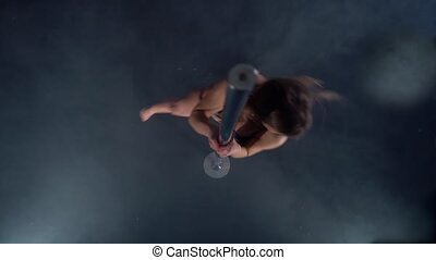 View from above of flexible woman dancing on pylon