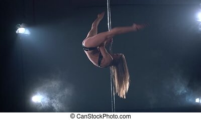 Pole dance. View of girl performs tricks on pylon