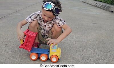 Happy little boy playing with toy car on the road at the day...