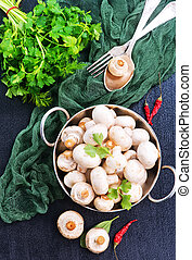 raw mushrooms in bowl and on a table