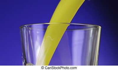 Orange juice pouring in glass on color background. slow...