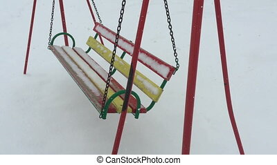 Empty swing in winter time with snow.