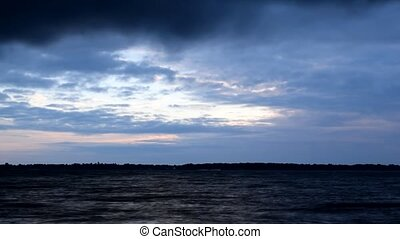 Beautiful blue clouds move fast over water at dawn