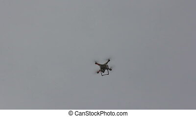 Quadrocopter unmanned camera hovers in bright blue sky .