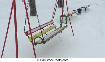 Empty swing in winter time with snow