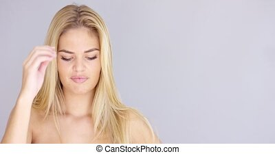 Cute sexy young woman posing isolated on gray. She smiling...