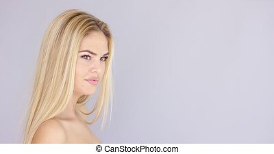 Young blond sexy girl posing on gray background. She...