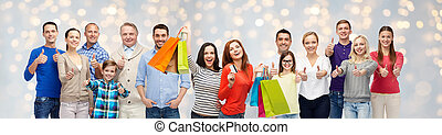 happy people with shopping bags showing thumbs up - sale,...