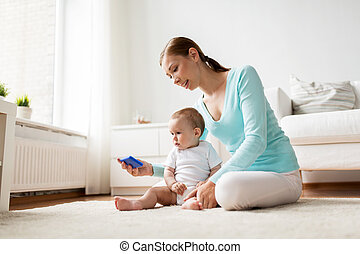 happy mother showing smartphone to baby at home - family,...