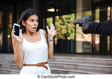 Scared woman holding cell phone threatened by criminal with...