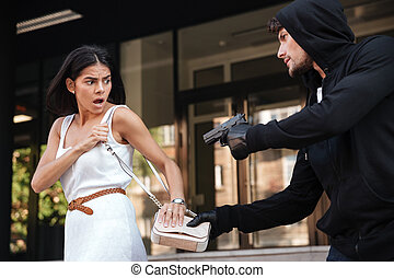 Criminal man with gun stealing bag of scared young woman