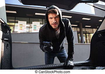 Criminal man threatening with gun and looking at car trunk -...