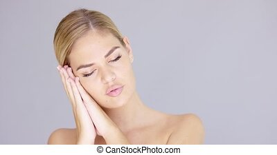 Pretty young blond woman making a sleep gesture resting her...