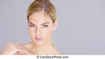 Sensual and sexy blond girl looking at camera while isolated...