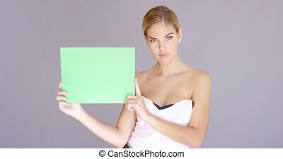 Happy attractive young woman with a blank sign