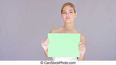 Attractive blond woman holding a blank green sign in front...