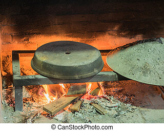 Old traditional stone bread oven stove with burning wood...