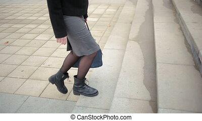female feet walking on the street. girl goes through the...