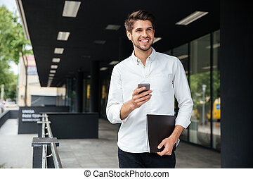 Businessman with smartphone and documents walking outdoors -...