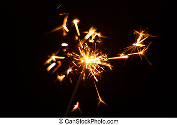 Sparkler on a black background, sparks fly in different directions,