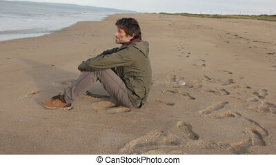 A middle aged man with a beard wearing grey pants, green jacket and yellow boots sitting on the sea shore and looking into the distance thoughtfully. He stands up an goes out of the frame.