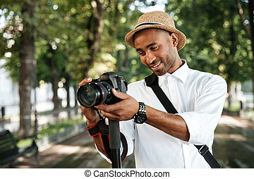Beautiful black man in park with camera
