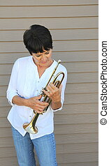 Female trumpet player. - Female trumpet player holding her...