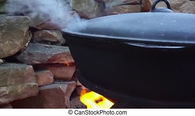 Cooking meat on a fire in cast-iron cauldron. - Cooking meat...