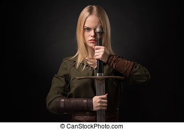 Woman warrior with sword in hand on gray background