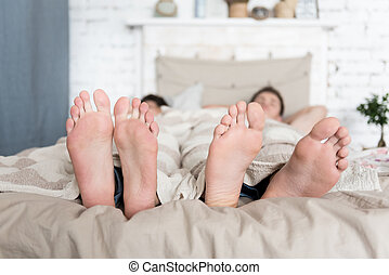 Close up of gay couples feet lying in bed