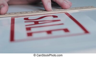 Man cutting sticker with red inscription SALE HD